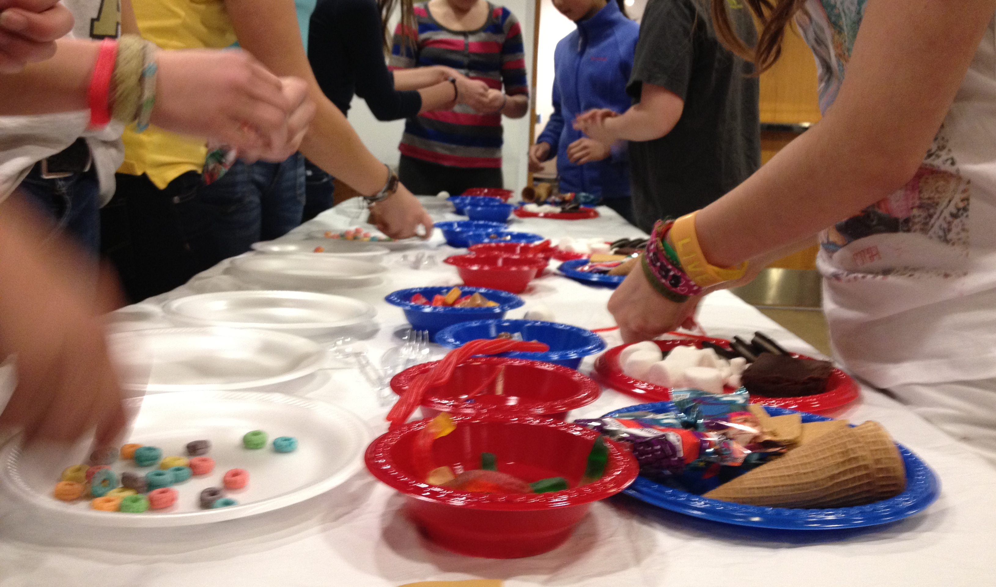 A photograph of teens from the shoulders down, gathered around a table covered in plates and bowls of candy and junk food, as they try to win a Teen Iron Chef competition