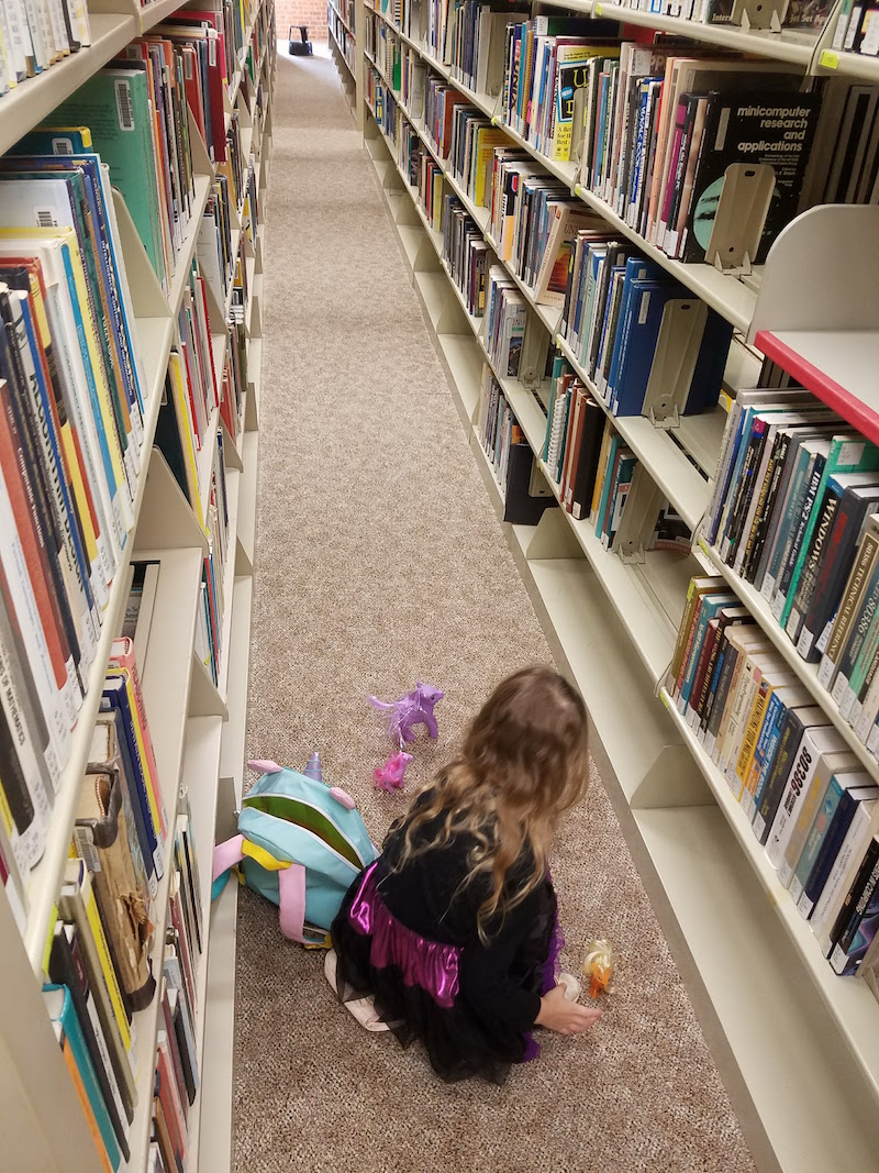 Author's daughter playing in library stacks
