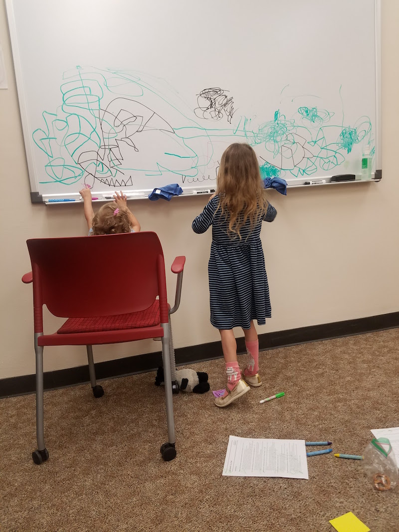 Author's daughters drawing on a whiteboard