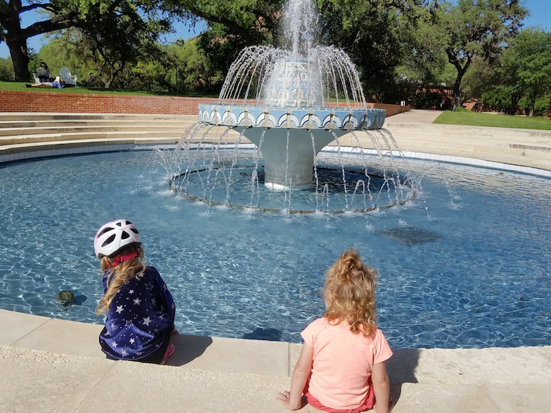 Author's daughters sitting at fountain